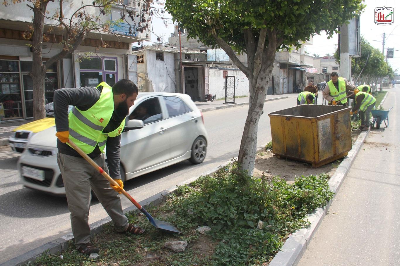 عمال النظافة أثناء قيامهم بأعمال تنظيف للجزيرة بشارع الشهداء- المحطة