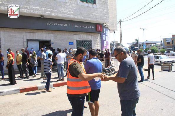 توزيع الكمامات الطبية على المواطنين أمام البنوك قبل استلام رواتبهم