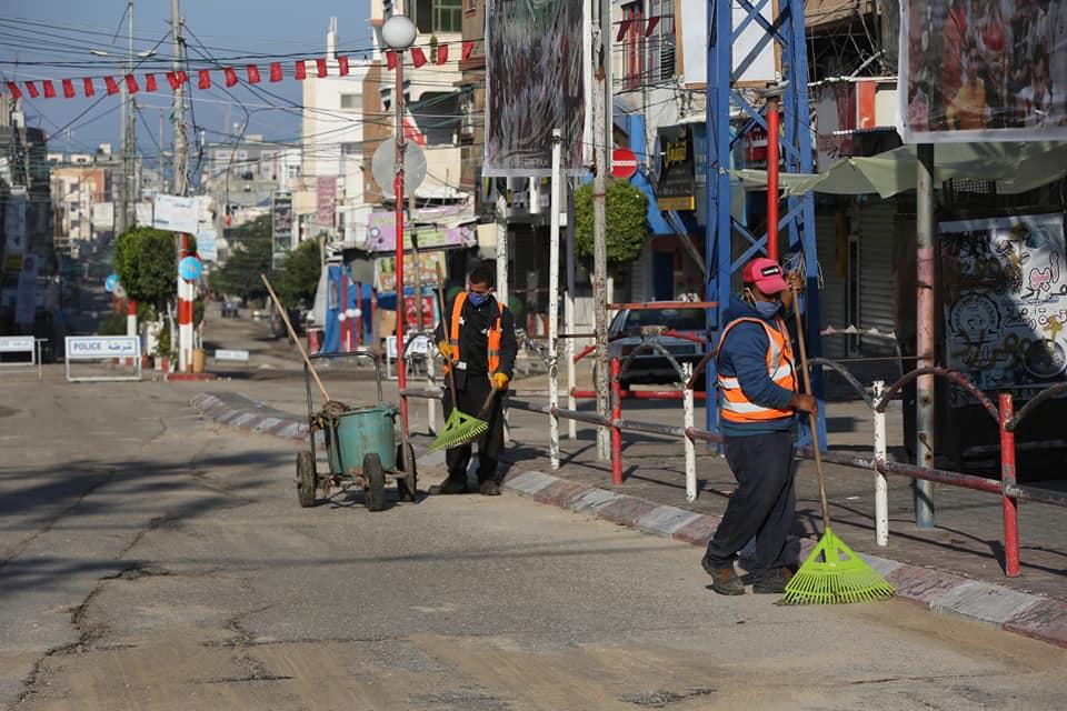 صناع الجمال ببلدية دير البلح وسط قطاع غزة يمارسون مهام تنظيف وجمع النفايات من مناطق المدينة خلال حظر