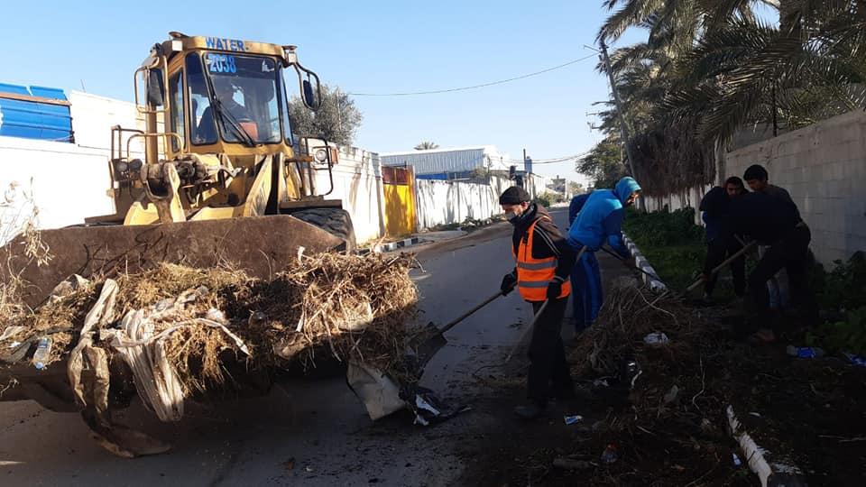 صناع الجمال ببلدية دير البلح وسط قطاع أثناء قيامهم بجمع النفايات و ترحيلها بالمنطقة الصناعية
