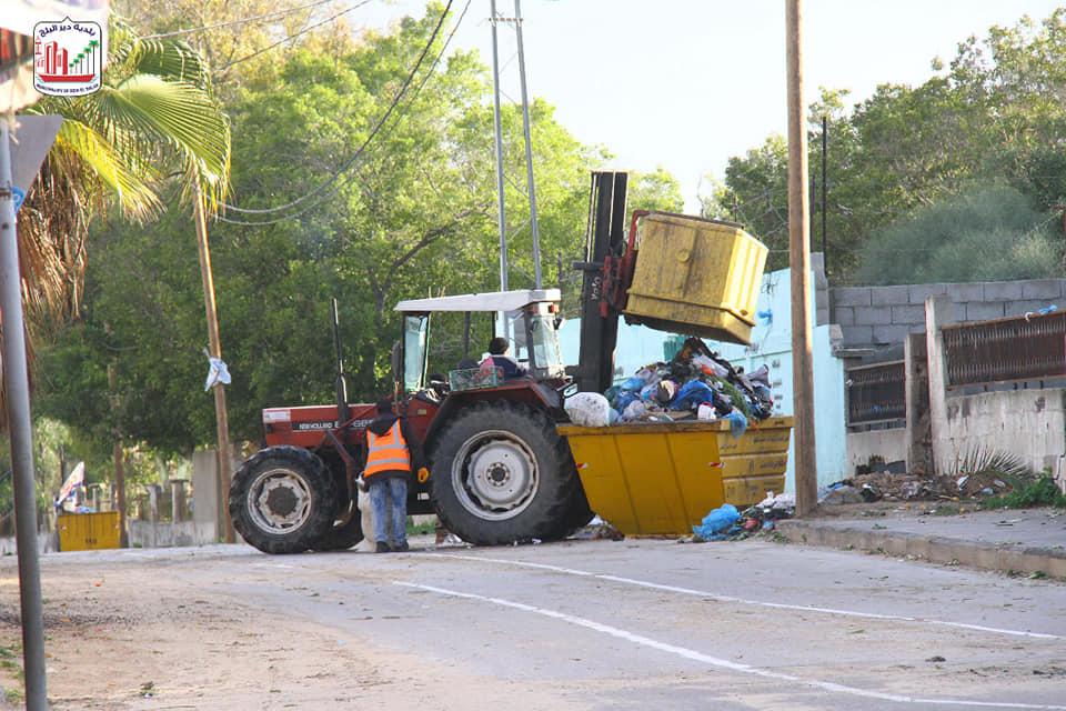 بالصور/ عمال النظافة ببلدية دير البلح مستمرين بعملهم في جمع وترحيل النفايات من مناطق وأحياء المدينة