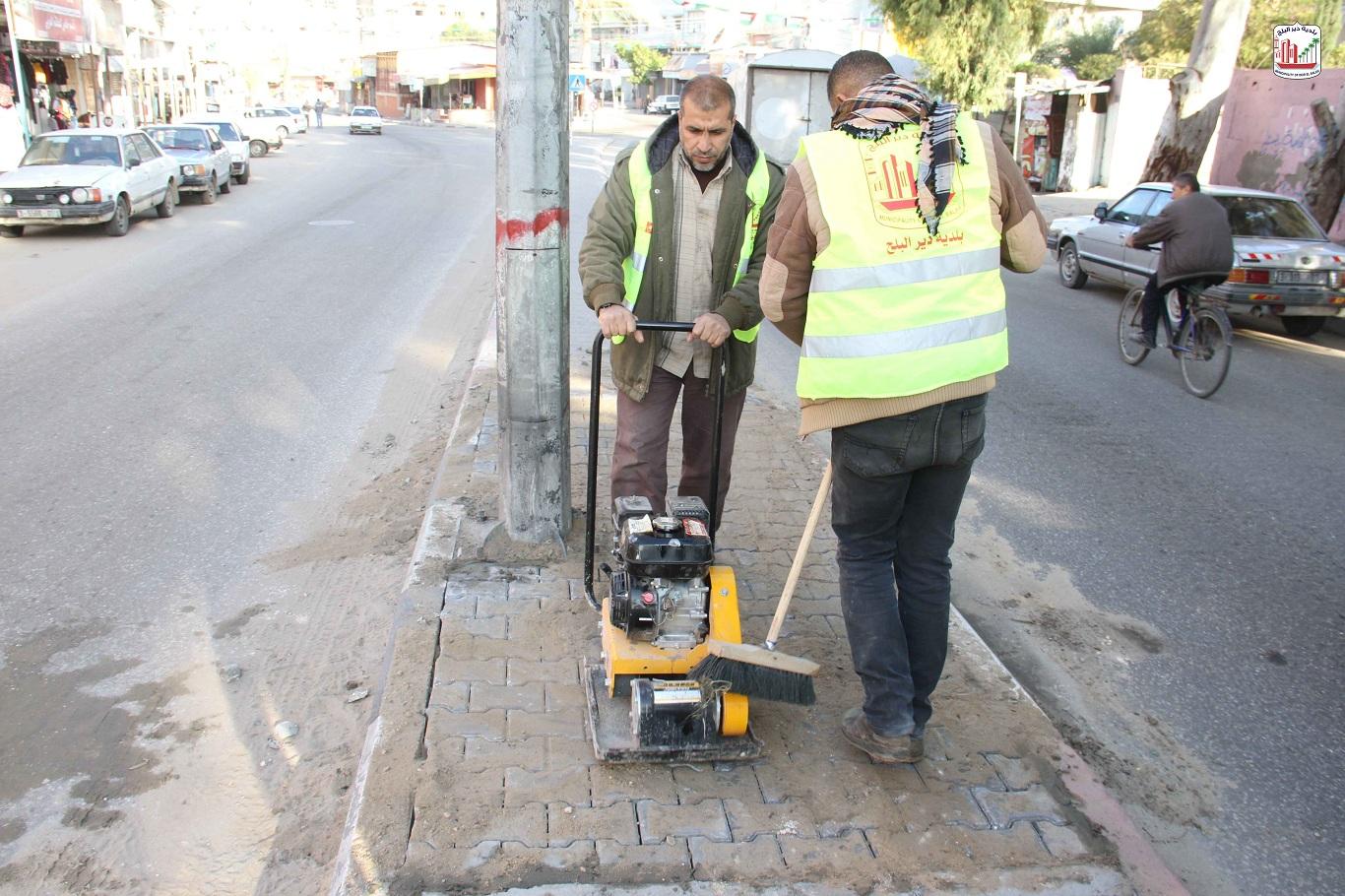 عمال قسم الصيانة أثناء قيامهم بأعمال صيانة بشارع الشهداء- المحطة