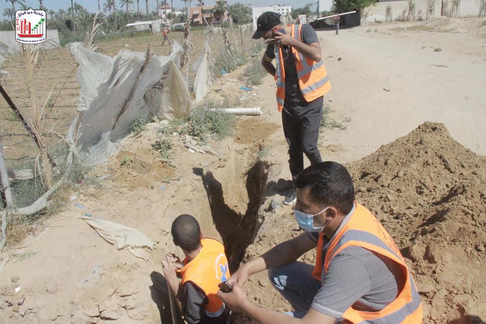 طواقم الصيانة ببلدية دير البلح خلال إصلاح خطوط المياه المتضررة جراء القصف الصهيوني
