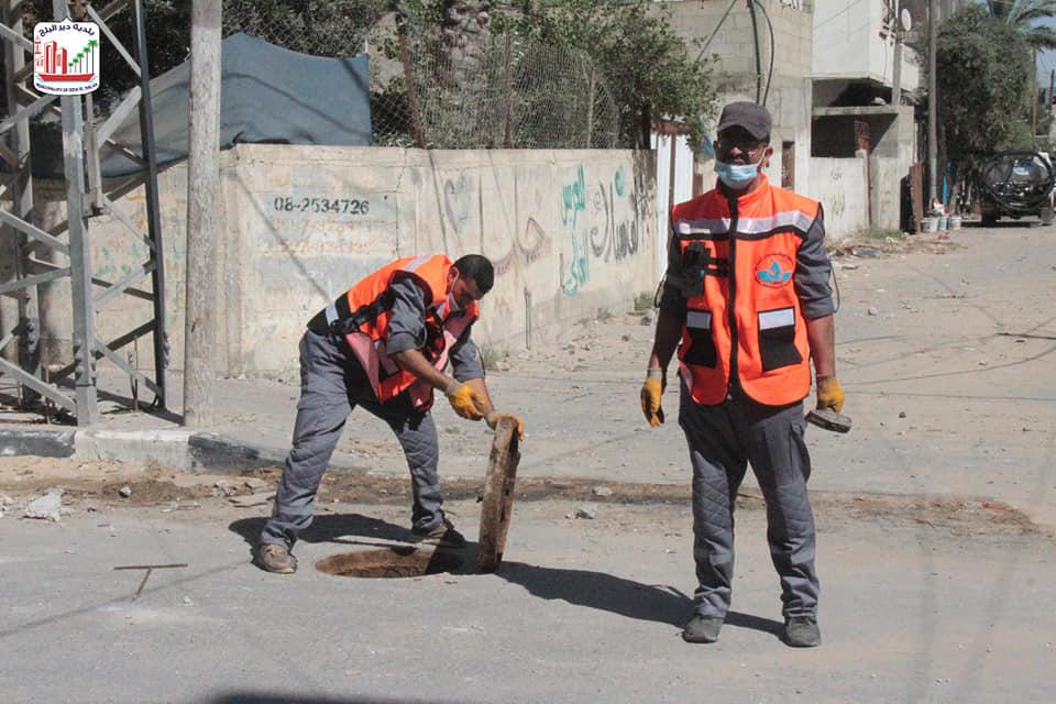 عمال الصرف الصحي ببلدية دير البلح خلال قيامهم بتسليك مناهل الصرف الصحي في الأماكن التي تعرضت للقصف ا