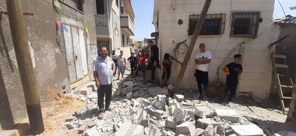 طواقم بلدية دير البلح خلال قيامها  بإزالة ركام ومخلفات القصف الصهيوني لأحد المنازل في المخيم