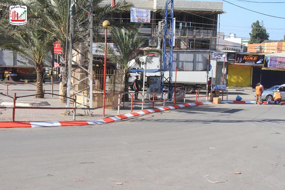 صناع الجمال ببلدية دير البلح خلال قيامهم بدهان حجر الجبهة وسط البلد وتحديد مواقف السيارت